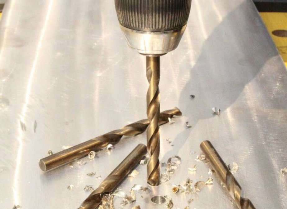 Drill bit boring a hole through a thick slab of metal