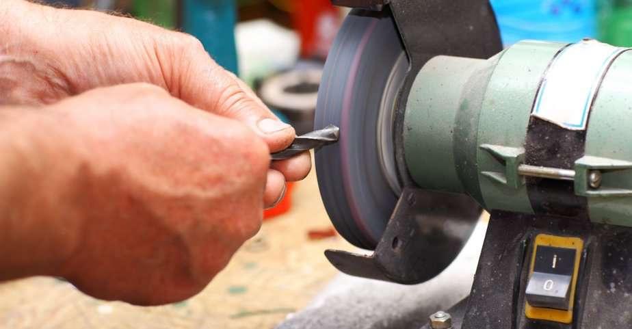 Worker re-sharpening black oxide drill bits